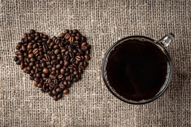 Koffiebonen hart en kopje koffie op linnen achtergrond.