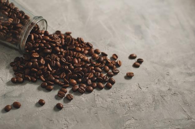 Koffiebonen in de pot op een grijze concrete achtergrond worden verspreid die