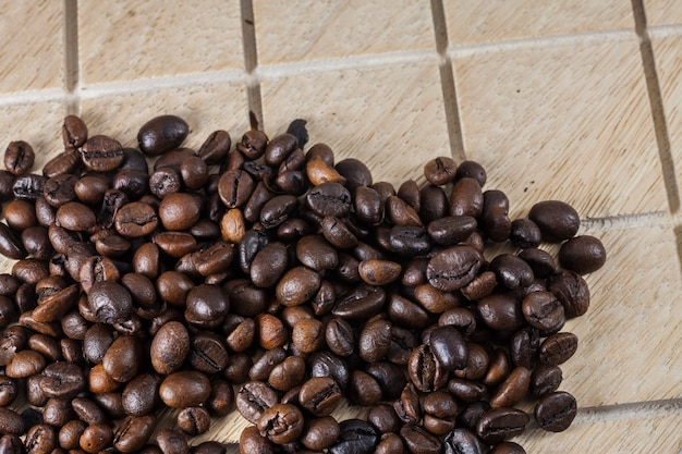 Koffiebonen in een bruine papieren zak op houten ondergrond.