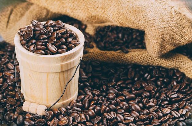 Koffiebonen in een emmer op een achtergrond van koffiebonen