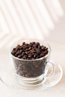 Koffiebonen in een glazen beker op een tafel.