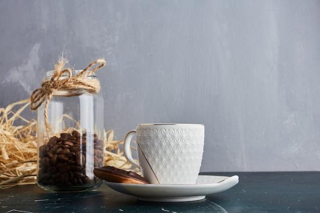 Koffiebonen in een houten beker in een glazen pot.