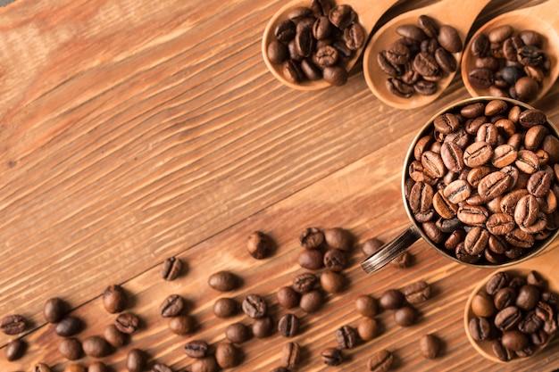 Koffiebonen in een houten lepel op rustieke achtergrond