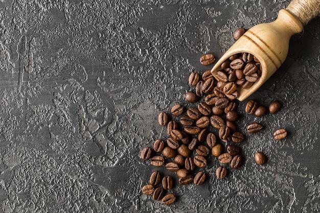 Koffiebonen in een houten lepel op steenachtergrond