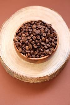 Koffiebonen in een houten ronde beker op een snee van een boom op een bruine tafel. koffiedrank. koffiebonen in een minimalistische stijl. bovenaanzicht