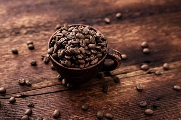 Koffiebonen in een kleikop op een bruine houten oude achtergrond.