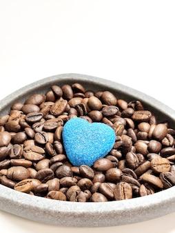 Koffiebonen in een kom en marmeladehart op een wit.