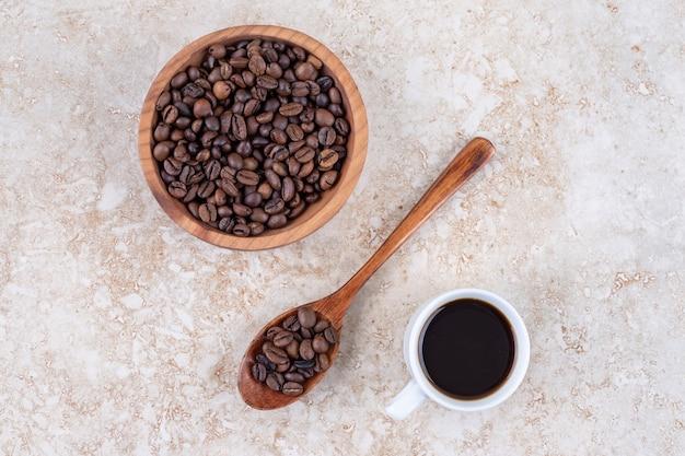 Koffiebonen in een kom en op een lepel naast een kopje koffie