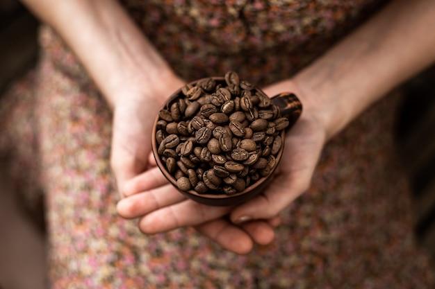Koffiebonen in een kopje in vrouwelijke handen op een bruine achtergrond.