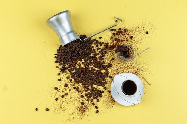 Koffiebonen in een kruik met glazen pot, kopje koffie plat lag op een gele achtergrond