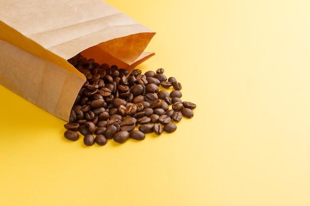 Koffiebonen in een papieren zak op een gele achtergrond