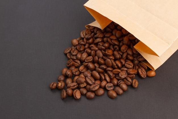 Koffiebonen in een papieren zak op een zwarte achtergrond