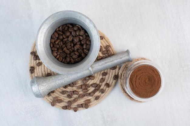 Koffiebonen in een vijzel en stamper met cacaopoeder