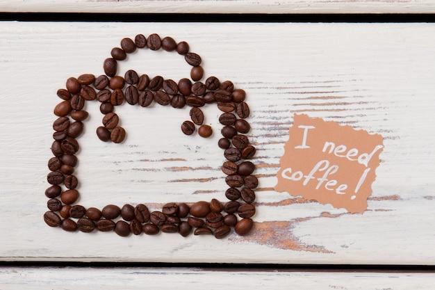 Koffiebonen in een vorm van pot op wit hout. ik heb koffieconcept nodig. abstracte vierkant met handvat.