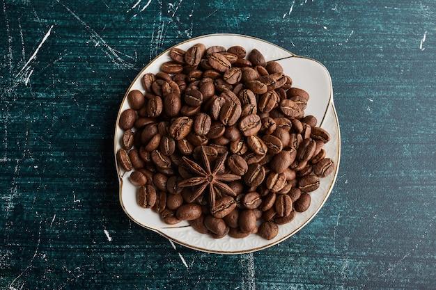 Koffiebonen in een witte keramische schotel.