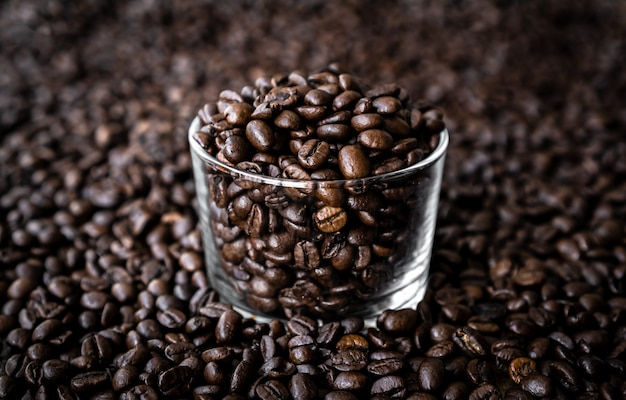 Koffiebonen in glas en achtergrond