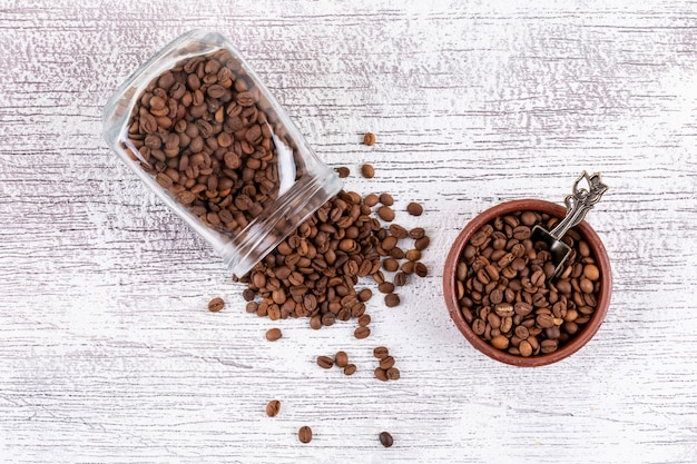 Koffiebonen in glaskruik en plaat op witte lijst