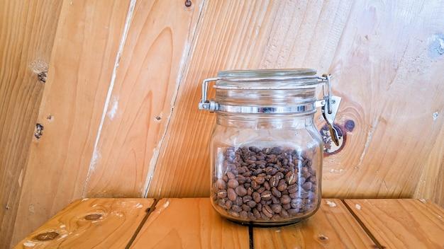 Koffiebonen in glazen pot op houten achtergrondkleur