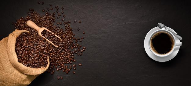 Koffiebonen in jutezak en kop van koffie op zwarte achtergrond