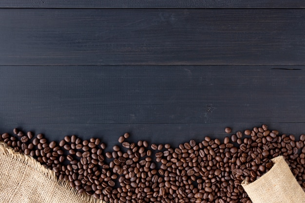 Koffiebonen in jutezak op oude houten achtergrond. bovenaanzicht