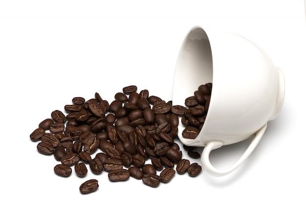 Koffiebonen in koffiekop op wit wordt geïsoleerd dat
