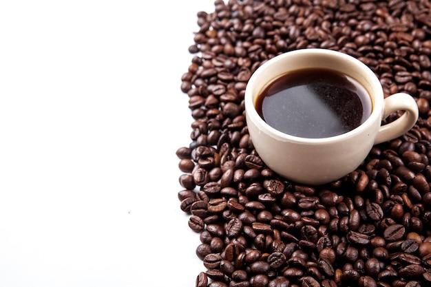 Koffiebonen in koffiekopje op wit wordt geïsoleerd