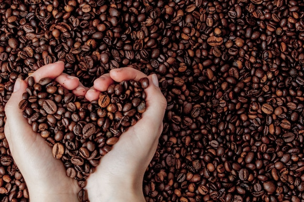 Koffiebonen in mensenpalmen in vorm van een hart op koffie.
