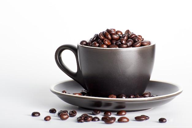 Koffiebonen in zwarte koffie, wit oppervlak