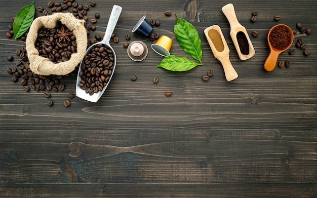Koffiebonen koffiecapsule en koffie poeder op donkere houten tafel.
