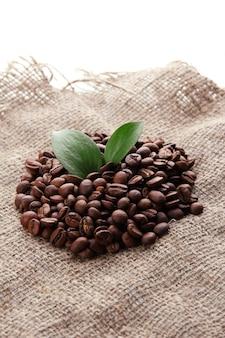 Koffiebonen met bladeren op jute