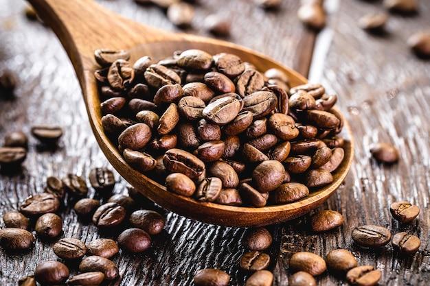 Koffiebonen met houten lepel, arabische koffie geselecteerd in hoge resolutie