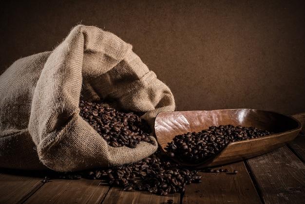 Koffiebonen met jutezak en bailer op grungeachtergrond