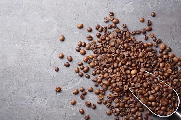 Koffiebonen met schep op grijze ondergrond