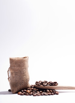Koffiebonen, met stoffen zak en houten lepel met wit.