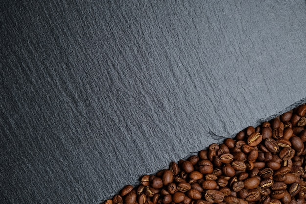Koffiebonen naast de achtergrond van de leisteenraad