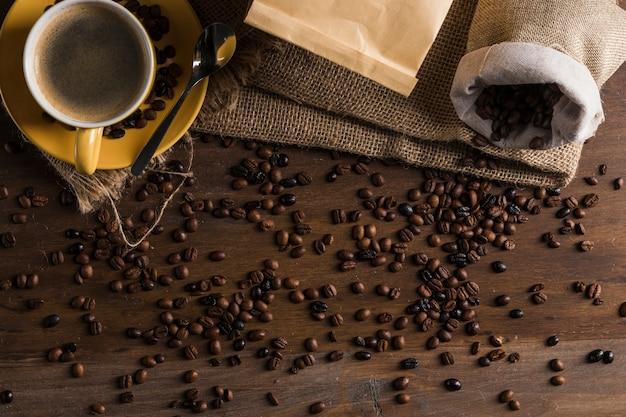 Koffiebonen op bureau met zak en kop worden geplaatst die