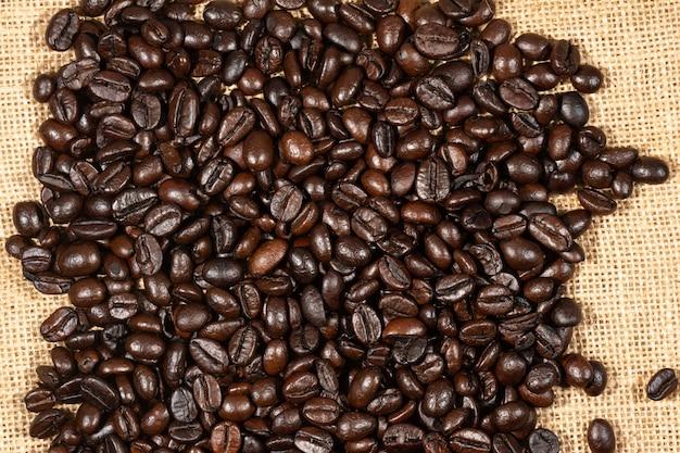 Koffiebonen op de bruine achtergrond van de linnenstof. de textuur van gebrande koffiebonen, die als achtergrond wordt gebruikt. plat lag, bovenaanzicht, kopie ruimte.