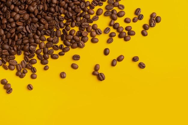Koffiebonen op een gele achtergrond, andere rond verspreide granen, concept