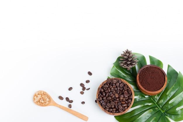 Koffiebonen op groene bladerensuiker op houten geïsoleerde lepel en pijnboom