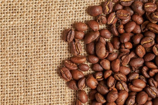 Koffiebonen op het gebreide materiaal voor exemplaarruimte. bovenaanzicht
