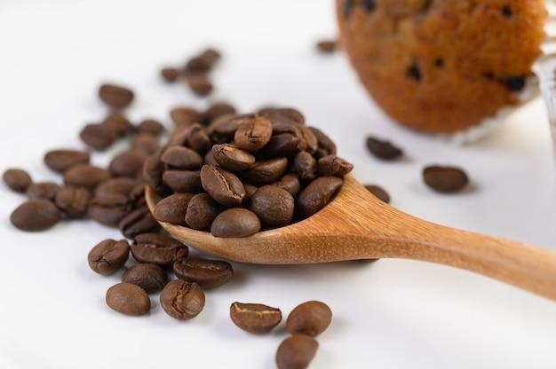 Koffiebonen op houten lepel en banaan cupcakes op een witte houten lijst.