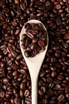 Koffiebonen op houten lepel en koffiebonenachtergrond.