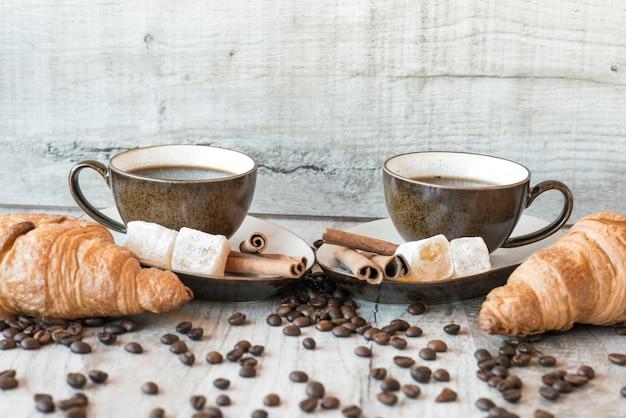 Koffiebonen op houten tafel met snoep en croissant