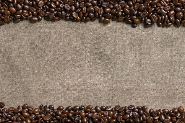 Koffiebonen op jute achtergrond. bovenaanzicht. ruimte kopiëren. stilleven. mock-up. plat leggen