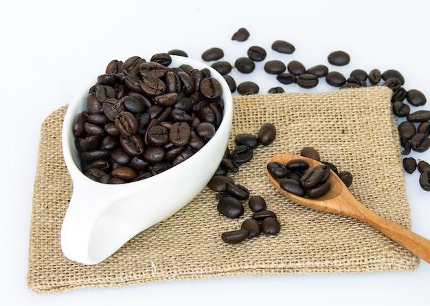 Koffiebonen op lepel en witte kop