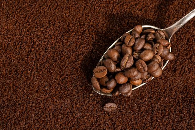 Koffiebonen op lepel op gemalen koffie. detailopname.