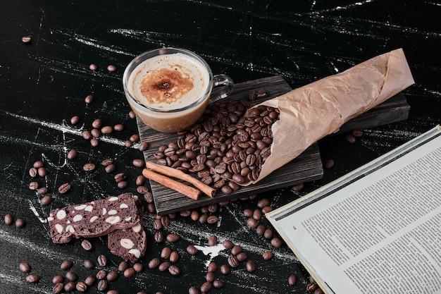Koffiebonen op zwarte achtergrond met drank en koekjes.
