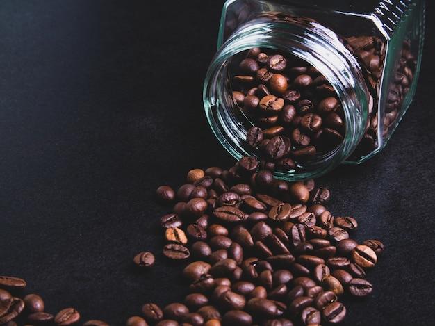 Koffiebonen uit een glazen pot op een zwarte achtergrond