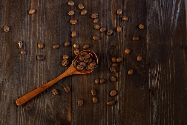 Koffiebonen verspreid over een donkere houten achtergrond met een houten lepel