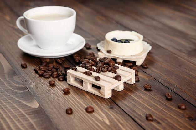 Koffiebonen verspreid over een houten standaard en een kopje koffie met bosbessencake. romantische sfeer.